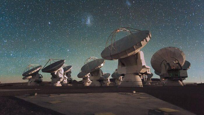 Varias grandes antenas parabólicas se agrupan bajo el cielo estrellado.